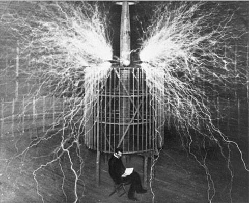 Nikola Tesla leyendo bajo una de sus bobinas