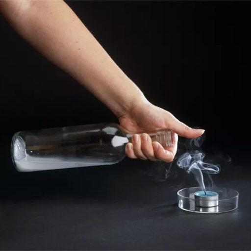 Botella con vinagre y bicarbonato vertiendo dióxido de carbono sobre vela para apagarla