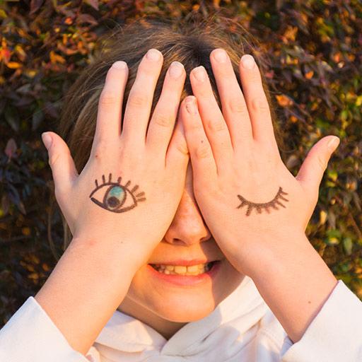 Chica con tatuajes en la palma de la mano cubriéndose los ojos